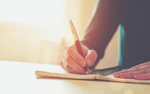 Frauenhand schreibt mit Kugelschreiber auf Block.